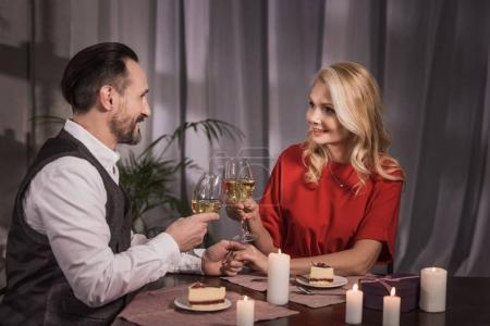 happy couple clinking with glasses of wine at home