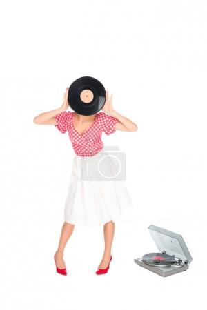 obscured view of woman in pin up style clothing covering face with vinyl record isolated on white