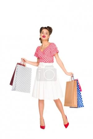 young woman in retro style clothing with shopping bags isolated on white