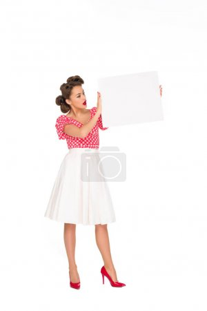 stylish woman looking at blank banner in hands isolated on white
