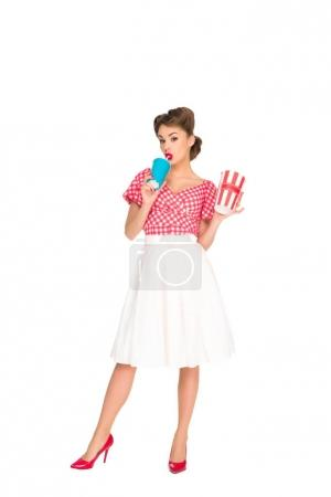 beautiful woman in retro style clothing with pop corn and drink in hands isolated on white