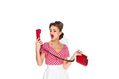 shocked pin up woman with old telephone isolated on white