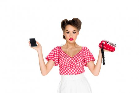 portrait of stylish woman in retro clothing holding smartphone and old telephone isolated on white