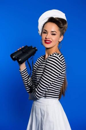 portrait of smiling young woman in retro clothing with binoculars isolated on blue