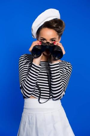 attractive young woman in retro clothing with binoculars isolated on blue
