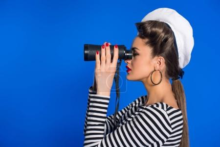 side view of attractive young woman in retro clothing with binoculars isolated on blue