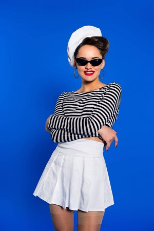 smiling stylish woman in retro clothing and sunglasses isolated on blue