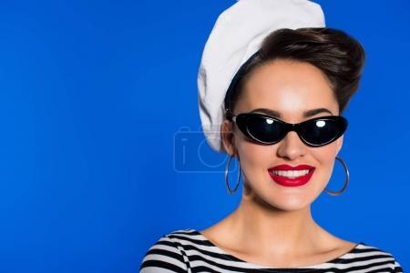 Photo pour Portrait de femme élégante souriante en vêtements rétro et lunettes de soleil isolées sur bleu - image libre de droit