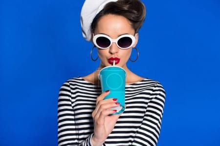 Foto de Retrato de mujer joven con estilo con bebida en taza de papel aislado en azul - Imagen libre de derechos