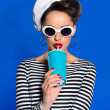 Portrait of stylish young woman with beverage in p...