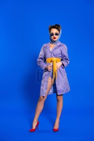 Photo pour Femme élégante en vêtements rétro et lunettes de soleil isolées sur bleu - image libre de droit
