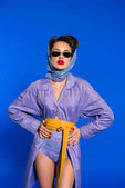 portrait of stylish woman in retro clothing and sunglasses standing akimbo isolated on blue
