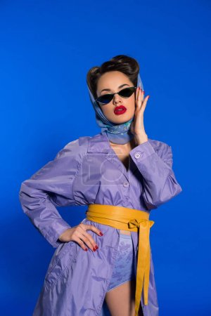 portrait of stylish woman in retro clothing and sunglasses isolated on blue