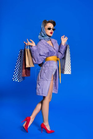 stylish woman in retro clothing with shopping bags isolated on blue