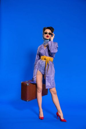 fashionable young woman in retro clothing with suitcase isolated on blue