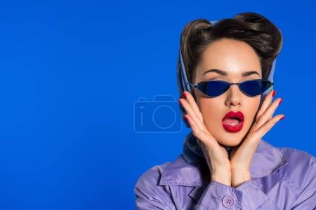 Photo for Portrait of stylish woman in retro clothing and sunglasses isolated on blue - Royalty Free Image