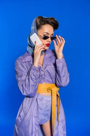 portrait of fashionable woman in retro style clothing talking on smartphone isolated on blue