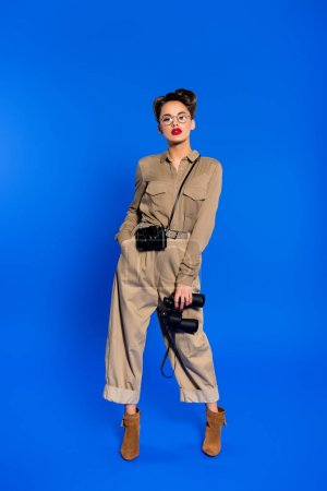 stylish young woman with binoculars and photo camera isolated on blue
