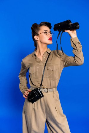 portrait of stylish young woman with binoculars and photo camera isolated on blue