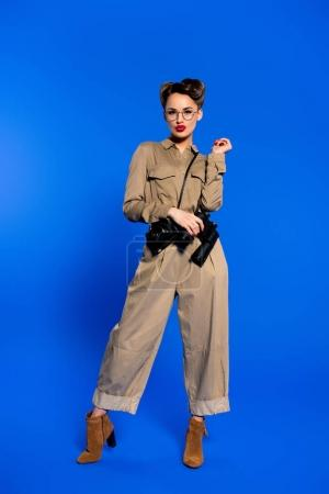 fashionable young woman in retro clothing with photo camera and binoculars isolated on blue
