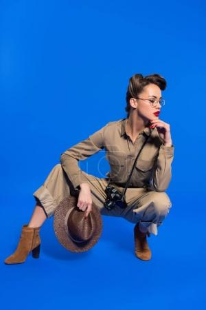 Photo for Stylish young woman in retro clothing with hat in hand isolated on blue - Royalty Free Image