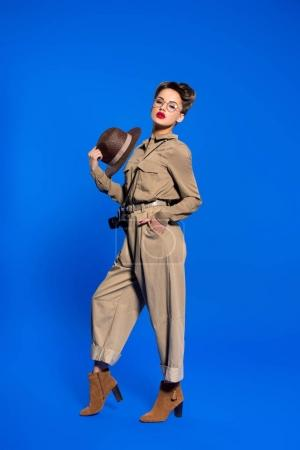 stylish young woman in retro clothing with hat in hand isolated on blue