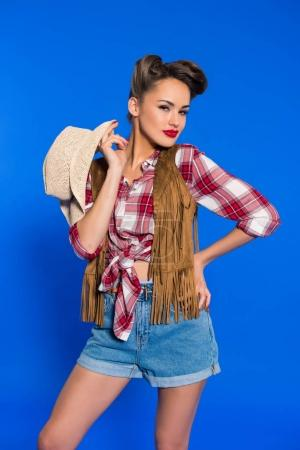 portrait of beautiful stylish woman with cowboy hat posing isolated on blue