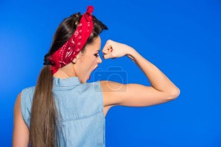 Photo pour Vue arrière du jeune femme en vêtements rétro, montrant les muscles isolés sur bleu - image libre de droit
