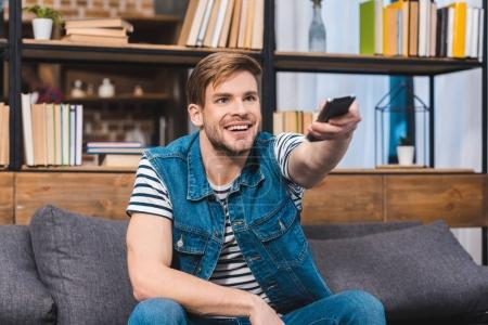 smiling young man using remote controller while sitting on sofa at home