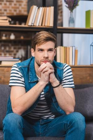 handsome young man sitting on sofa and looking away