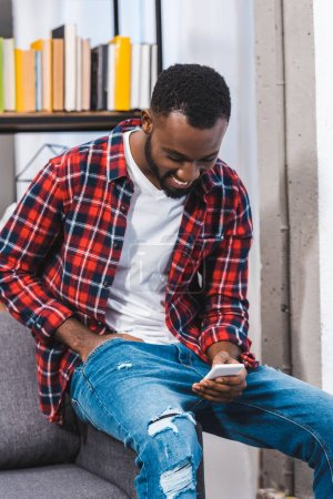 Photo for Smiling young african american man using smartphone at home - Royalty Free Image