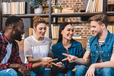 Photo for Happy young multiethnic friends playing game of rock, paper, scissors - Royalty Free Image