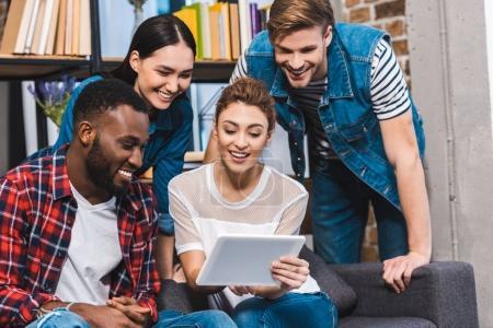 Photo pour Heureux jeunes amis multiethniques à l'aide de tablette numérique ensemble - image libre de droit