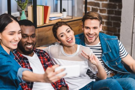 happy young multiethnic friends taking selfie with smartphone