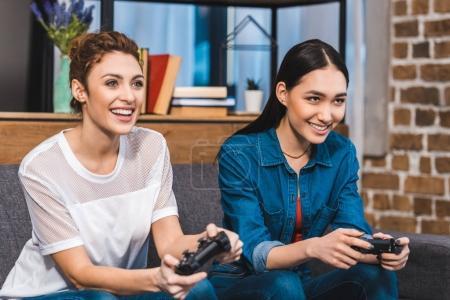 Foto de Hermosa sonriendo a multiétnicas niñas jugando con palancas de mando juntos - Imagen libre de derechos