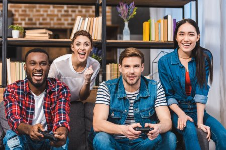 cheerful young multiethnic friends playing with joysticks together at home