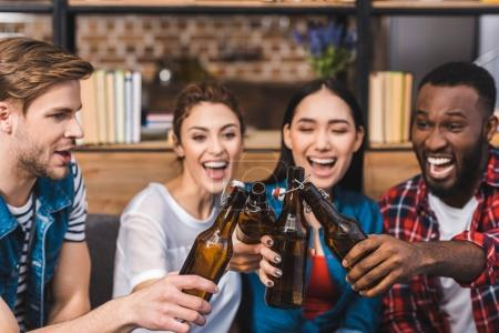 happy young multiethnic friends clinking beer bottles