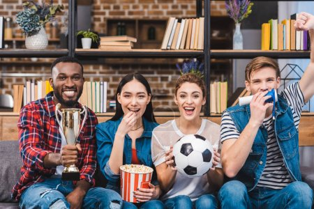 Photo for Happy young multiethnic friends watching soccer match together at home - Royalty Free Image