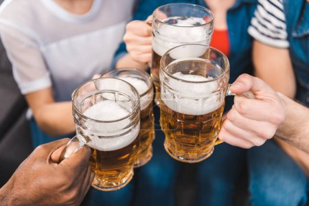 Photo for Close-up partial view of young friends holding glasses of beer in hands - Royalty Free Image