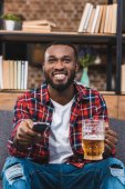 cheerful young african american man holding glass of beer and remote controller at home