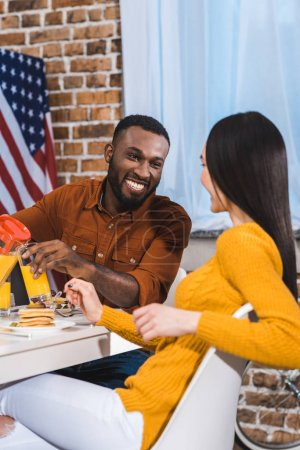 young multiethnic couple smiling each other while having breakfast together at home