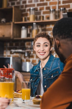 Photo for Cropped shot of smiling young multiethnic couple having breakfast together at home - Royalty Free Image