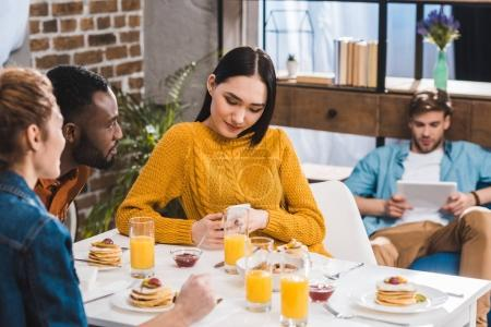 cropped shot of multiethnic friends looking at asian girl using smartphone at table and young man using digital tablet behind