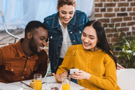smiling young multiethnic friends using smartphone together