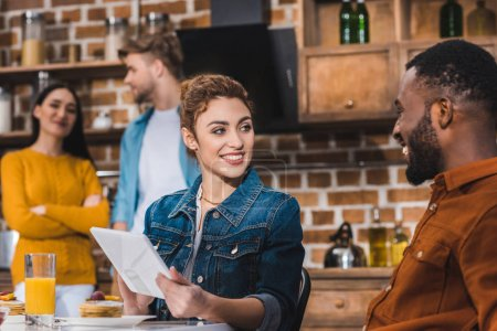 happy young multiethnic couple using digital tablet at table with juice and pancakes