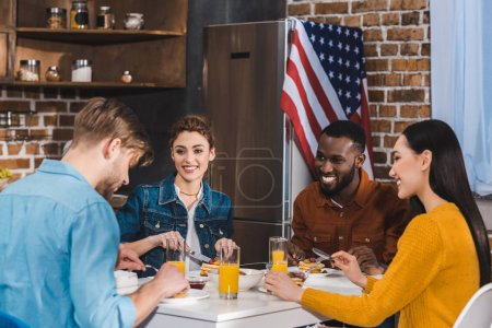 happy young multiethnic friends eating pancakes and drinking juice together