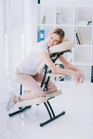 smiling beautiful woman sitting on massage chair at office