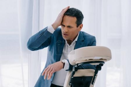 Photo pour Homme mature avec headahce se penchant sur le fauteuil de massage - image libre de droit
