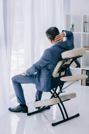 rear view of businessman with painful backache sitting in massage chair at office