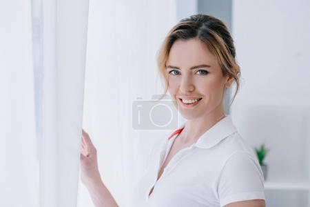 attractive adult woman standing near window